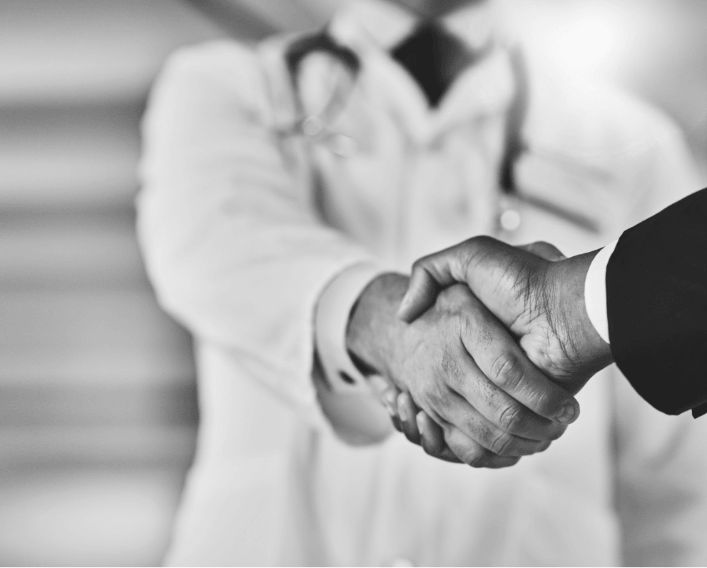 """Doctor shaking hands with business person 