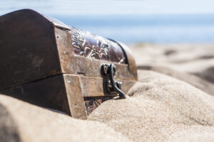 close-up-locked-chest-in-the-sand-on-the-beach