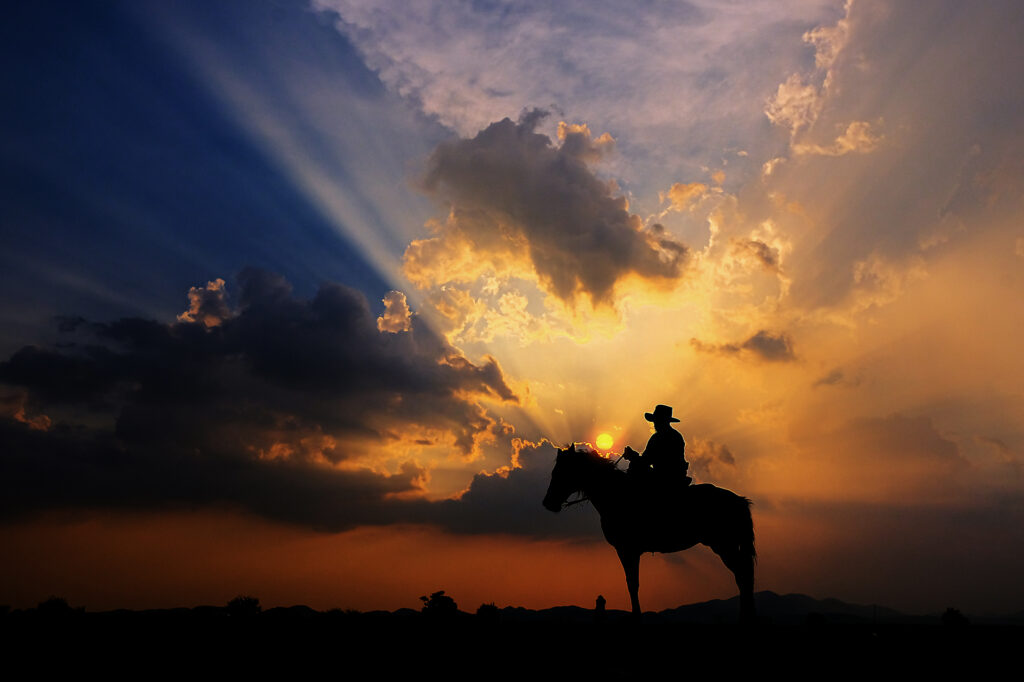 the-silhouette-of-a-cowboy-on-horseback-at-sunset-on-a-background